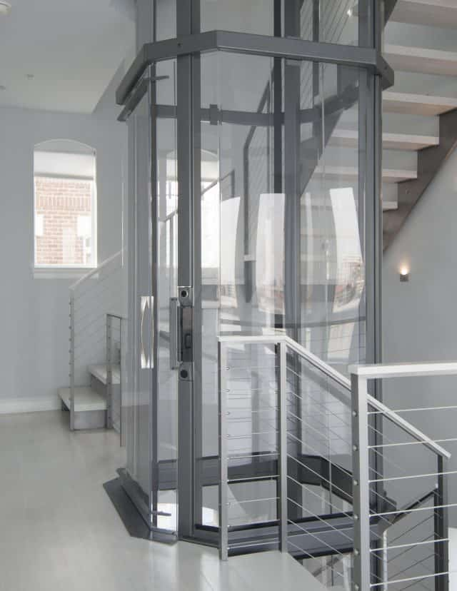 savaria vuelift octagonal glass elevator on the 2nd story landing of a 3-story Townhome adjacent to wrap-around stairs