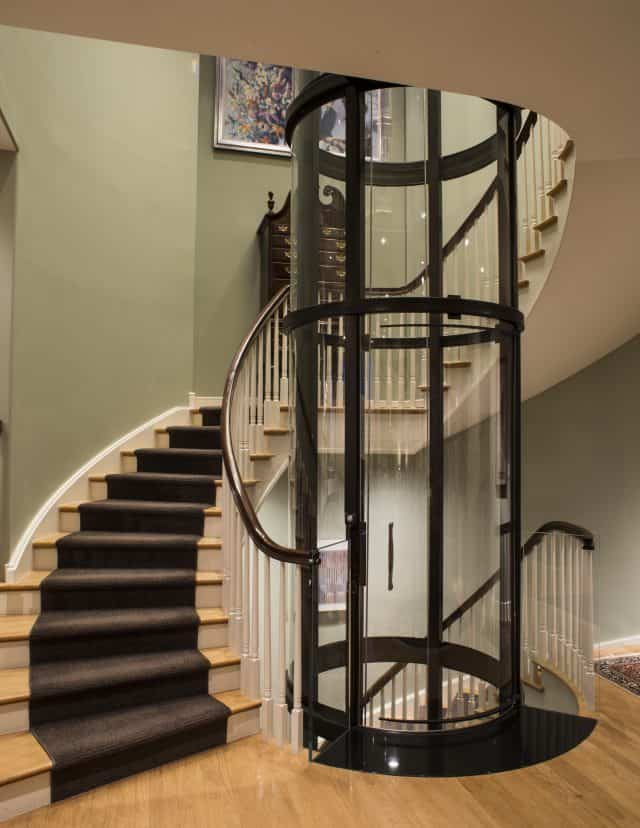 savaria vuelift round glass elevator instlled in a starwell of a circular staircase